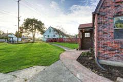 Small red brick home on a sunny day. View of covered front porch. Northwest, USA Royalty Free Stock Image