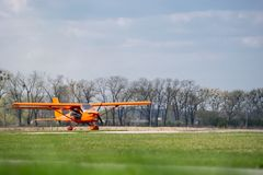 Small red charter airplane waiting on a green field to take off.  stock photos
