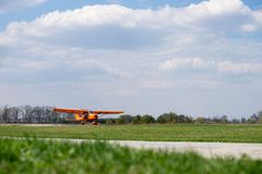 Small red charter airplane waiting on a green field to take off.  royalty free stock photos