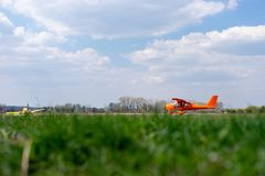 Small red charter airplane waiting on a green field to take off.  royalty free stock image