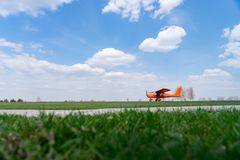 Small red charter airplane waiting on a green field to take off.  royalty free stock photo