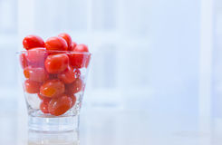Small red cherry tomatoes in clear glass cup. Small red cherry tomatoes in wet clear glass cup on white table with blur background, concept for healthy diet Stock Images