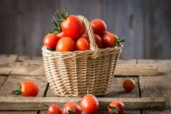 Small red cherry tomatoes  in a small wicker basket Royalty Free Stock Photo