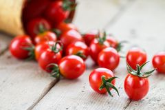 Small red cherry tomatoes spill out of a wicker basket. On an old wooden table in rustic style, selective focus Royalty Free Stock Photos