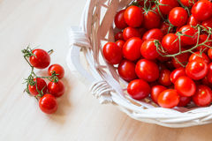 Small red cherry tomatoes in a wicker basket on an old wooden table. A view of small red cherry tomatoes in a wicker basket on an old wooden table Stock Photo