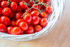 Small red cherry tomatoes in a wicker basket on an old wooden table. A view of small red cherry tomatoes in a wicker basket on an old wooden table Stock Photography
