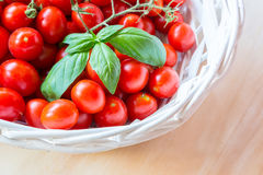 Small red cherry tomatoes in a wicker basket on an old wooden table. A view of small red cherry tomatoes in a wicker basket on an old wooden table Royalty Free Stock Image