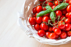 Small red cherry tomatoes in a wicker basket on an old wooden table. A view of small red cherry tomatoes in a wicker basket on an old wooden table Royalty Free Stock Photos