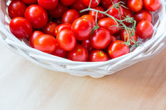 Small red cherry tomatoes in a wicker basket on an old wooden table. A view of small red cherry tomatoes in a wicker basket on an old wooden table Royalty Free Stock Images
