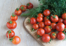 Small red cherry tomatoes on a wooden surface. Country style. Bright dill Royalty Free Stock Photos