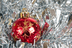 Small red christmas ball. Over silver tinsel Royalty Free Stock Image