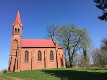 Red church on a hill in Strzepowo Poland. A small red church on a green hill on sunny spring day with clear blue sky. Strzepowo, northern Poland Royalty Free Stock Images