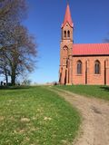 Red church on a hill in Strzepowo Poland. A small red church on a green hill on sunny spring day with clear blue sky. Strzepowo, northern Poland Royalty Free Stock Photo