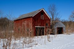 Small Red Corn Crib. This is a Winter picture of a small red corn crib and an tractor building on a hillside in LaSalle County, Illinois. This picture was taken stock photos