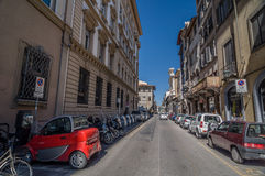Small red electric car on street Borgo Ognissanti in Florence. royalty free stock photography