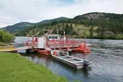 Small red ferry on the mountain river on the forest and hills background royalty free stock images