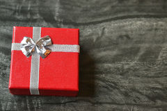 Small red gift box on marble table. Small red gift box with silver ribbon on black marble table Stock Photos
