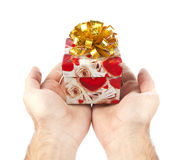 Small red gift in palms of hands Stock Photo