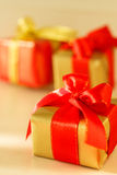 Small red and golden boxes with gifts tied bows Stock Photo