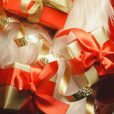 Small red and golden boxes with gifts tied bows Royalty Free Stock Images