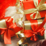 Small red and golden boxes with gifts tied bows Stock Images