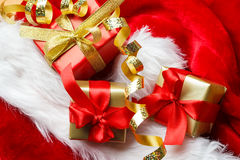 Small red and golden boxes with gifts tied bows Stock Photos