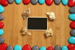 Small red gray and blue pebbles arranged all around a brown bamboo wood floor with in the center an empty slate to write a message. Red gray and blue pebbles Stock Image