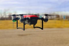 Small red and grey drone in flight  with three fourths battery charge against blurred background - winter. Scene Stock Photos