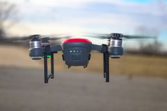 Small red and grey drone with landing gear attached and battery at half charge flying against blurred background. And sky Royalty Free Stock Photos
