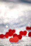 Small red hearts on snow Royalty Free Stock Photography