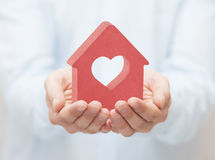 Small red house with heart in hands Royalty Free Stock Image