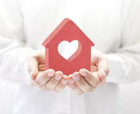 Small red house with heart in hands Stock Image