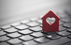 Small red house with heart over keyboard Stock Images