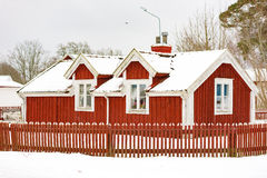 Small red house. Johannishus, Sweden - January 8, 2016: A small red wooden house with fence and snow covered roof. These kind of houses are often considered Stock Photo
