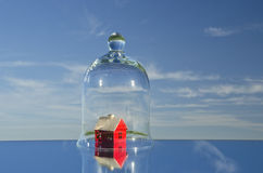 Small red house model in glass bell on mirror in space Royalty Free Stock Photos