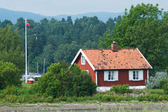 Small, red house in Norway. Small, old, red house by the sea in Norway, with Norwegian pennant flying and sailboat masts visible in the background Stock Photos