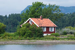 Small, red house by the sea Stock Photography