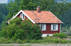 Small, red house among trees Royalty Free Stock Photos