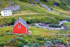 A small red house in village in Norway. A red house stand in a small village in Norway. around it is green grass and river Stock Photography