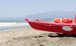 Small red life guard vessel is parking next to the sea Royalty Free Stock Images