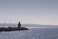 Small red lighthouse near a sea Royalty Free Stock Photography