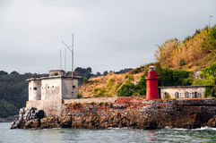 Small red lighthouse and old house Royalty Free Stock Images