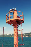 Small red lighthouse pole on the coast of Sea Royalty Free Stock Image