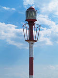 Small red lighthouse tower over cloudy blue sky Stock Photography