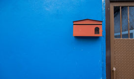 Small red mailbox on the blue wall house Royalty Free Stock Images