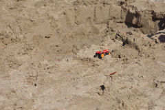 Small red metal toy tractor on the wet sand beach. Summer vacati Stock Images