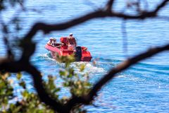 Small red motorboat departs from the seashore with people on board. Tourist transportation service at Anapa sea resort. Scenic. Anapa, Russia - June 11, 2012 stock image