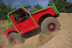 Small red off road car is hitting a steep hill Stock Photo