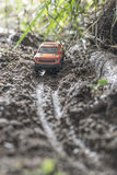Small red off road car toy in the nature. Royalty Free Stock Image