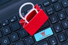 Small red paper shopping bags on laptop keyboard.Wait for the cu royalty free stock photo